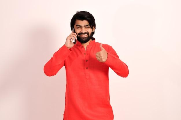 Jonge indiase man met kurta praten op een smartphone en duimen opdagen