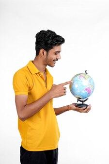 Jonge indiase man met palmen aarde wereldbol in de hand