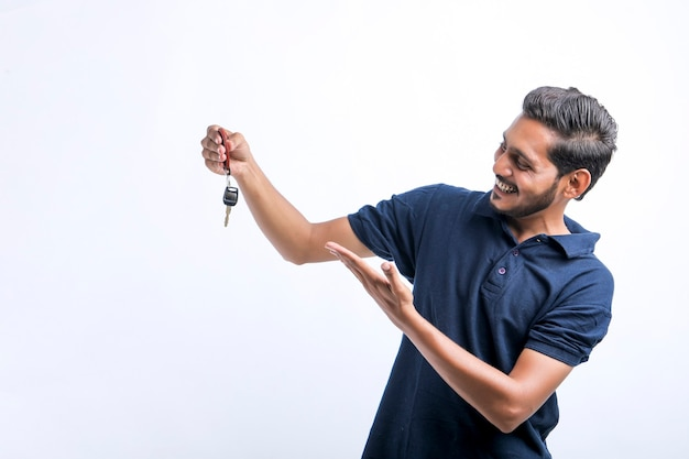 Jonge indiase man met sleutel in de hand op witte achtergrond.