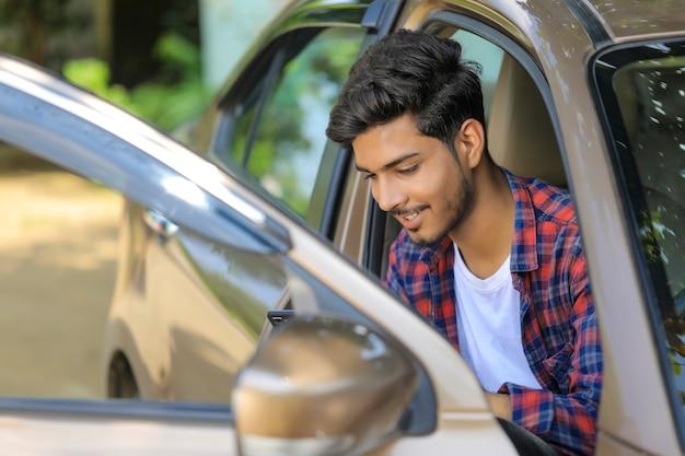 Jonge indiase man met zijn auto