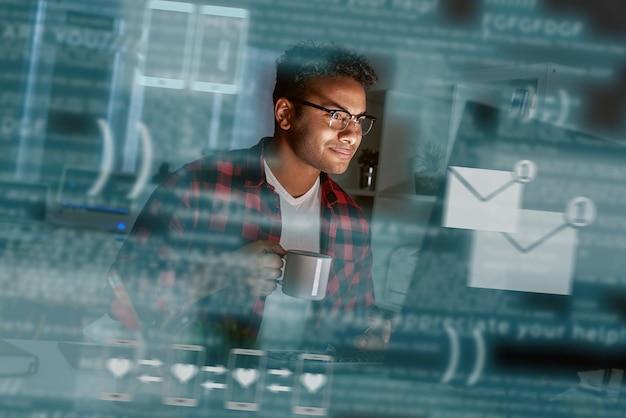 Jonge indiase man ontving bericht van populaire dating-app. hij draagt een bril en glimlacht. er is koffieoogst in zijn handen