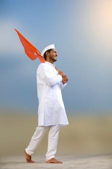 Jonge indiase man (pelgrim) in traditionele slijtage en wuivende religieuze vlag.