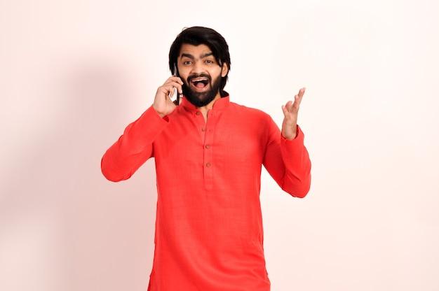 Jonge indiase man praat op smartphone en viert gek en verbaasd over succes met open ogen