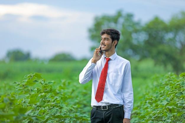 Jonge indiase man praten op mobiele telefoon