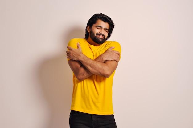 Jonge indiase man verliefd voelen glimlachen knuffelen en knuffelen zichzelf single blijven egoïstisch zijn
