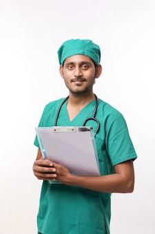 Jonge indiase mannelijke arts in uniform met stethoscoop die notities maakt in kladblok op witte achtergrond.