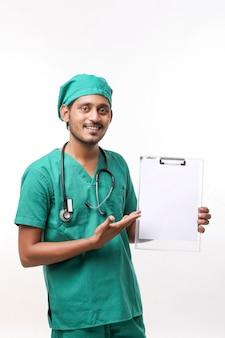 Jonge indiase mannelijke arts in uniform met stethoscoop met kladblok op witte achtergrond.