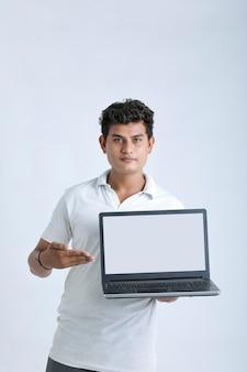 Jonge indiase succesvolle man laptop scherm tonen op witte achtergrond.