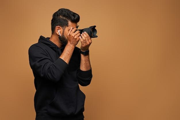 Jonge indiase videograaf in zwarte hoody met camera aan de muur
