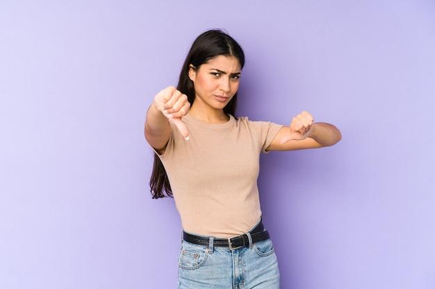 Jonge indiase vrouw die duim toont en afkeer uitdrukt.