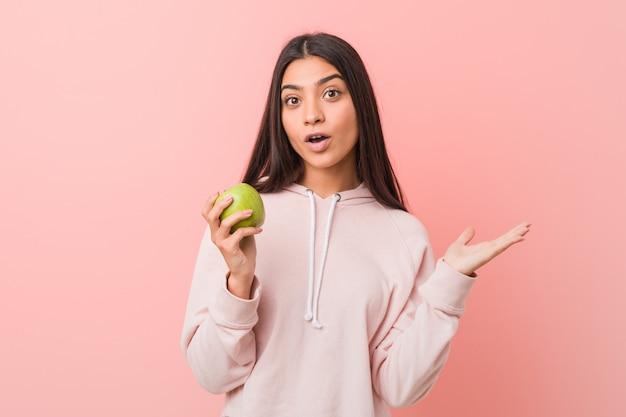 Jonge indiase vrouw die een appel eet