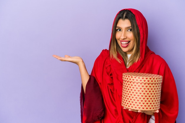 Jonge indiase vrouw die een hijab draagt die een valentijnsdag geschenk houdt geïsoleerd met een kopie ruimte op een palm en een andere hand op de taille houdt.