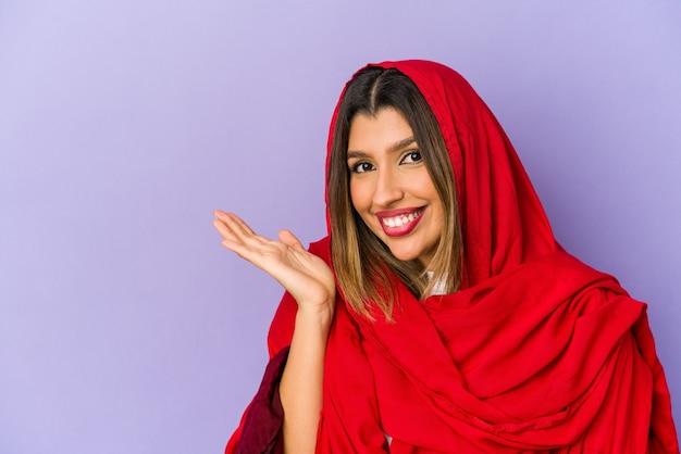 Jonge indiase vrouw die een hijab draagt geïsoleerd met een kopie ruimte op een palm en een andere hand op de taille houdt.