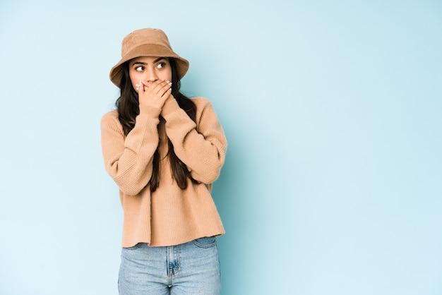 Jonge indiase vrouw die een hoed draagt die nadenkend aan een exemplaarruimte kijkt die mond behandelt met hand.
