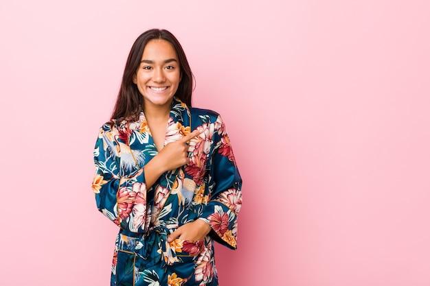 Jonge indiase vrouw die een kimonopyjama draagt die opzij glimlacht en wijst, iets op lege ruimte toont.