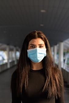 Jonge indiase vrouw die een masker draagt ter bescherming tegen de uitbraak van het coronavirus bij de voetgangersbrug