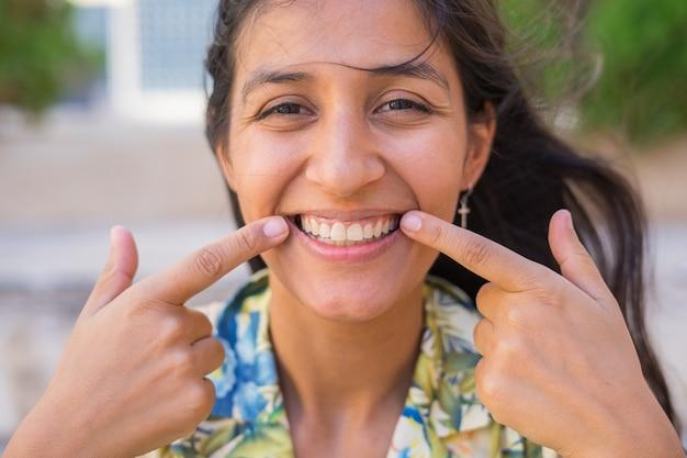 Jonge indiase vrouw die haar glimlachend aanwijst