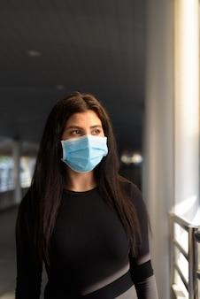 Jonge indiase vrouw die met masker denkt ter bescherming tegen de uitbraak van het coronavirus bij de voetgangersbrug
