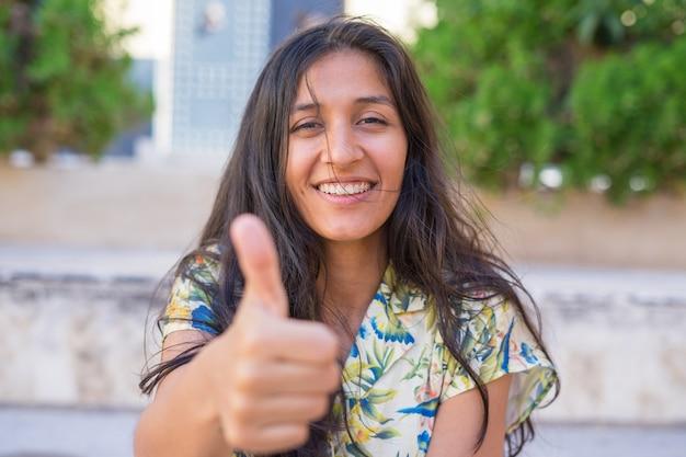 Jonge indiase vrouw duim omhoog op straat