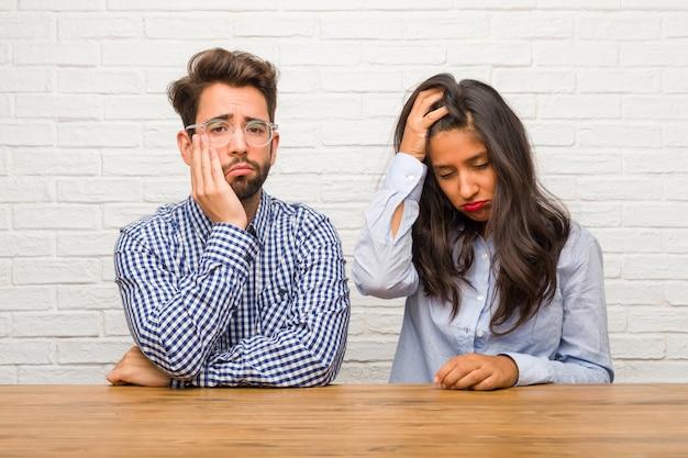 Jonge indiase vrouw en blanke man paar bezorgd en overweldigd, vergeetachtig, realiseren iets, uitdrukking van schok op het hebben van een fout
