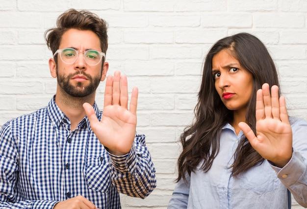 Jonge indiase vrouw en blanke man paar serieus en vastberaden, hand in de voorkant, stop gebaar, ontkennen concept