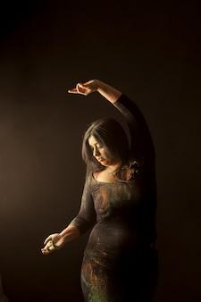 Jonge indiase vrouw geïsoleerd dansen en spelen met gekleurd stof in donkere kleding