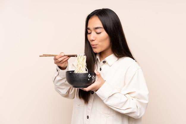 Jonge indiase vrouw geïsoleerd op beige achtergrond met een kom noedels met eetstokje zand blazen omdat ze heet zijn