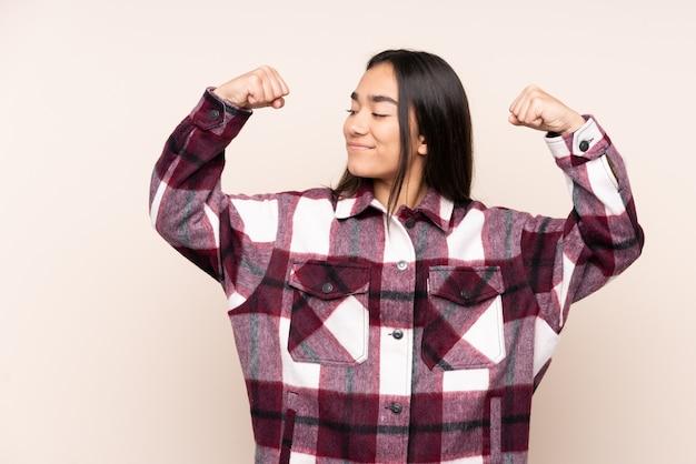 Jonge indiase vrouw geïsoleerd op beige doet sterk gebaar