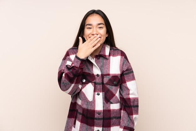 Jonge indiase vrouw geïsoleerd op beige gelukkig en glimlachend bedekkende mond met hand