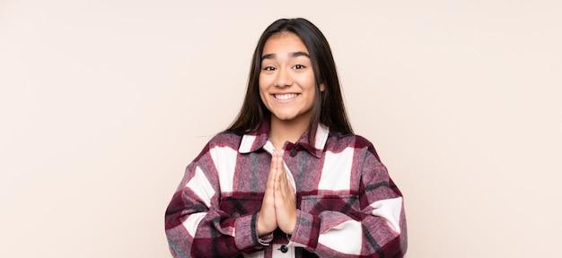 Jonge indiase vrouw geïsoleerd op beige houdt palm bij elkaar. persoon vraagt iets