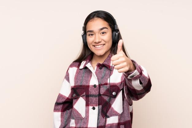 Jonge indiase vrouw geïsoleerd op beige luisteren muziek en met duim omhoog