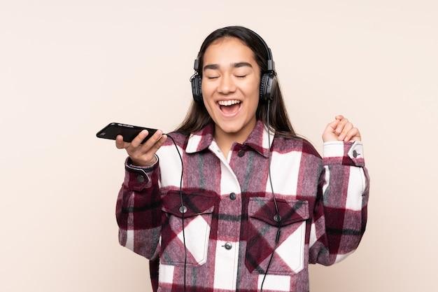 Jonge indiase vrouw geïsoleerd op beige muziek luisteren met een mobiele telefoon en zingen