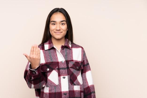 Jonge indiase vrouw geïsoleerd op beige uitnodigend om met de hand te komen. blij dat je gekomen bent