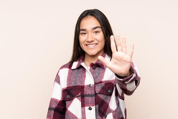 Jonge indiase vrouw geïsoleerd op beige vijf tellen met vingers