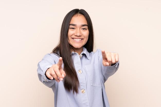 Jonge indiase vrouw geïsoleerd op beige wijzende voorkant met gelukkige uitdrukking