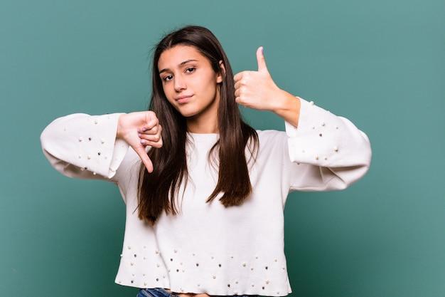 Jonge indiase vrouw geïsoleerd op blauw met duimen omhoog en duim omlaag, moeilijk kies concept