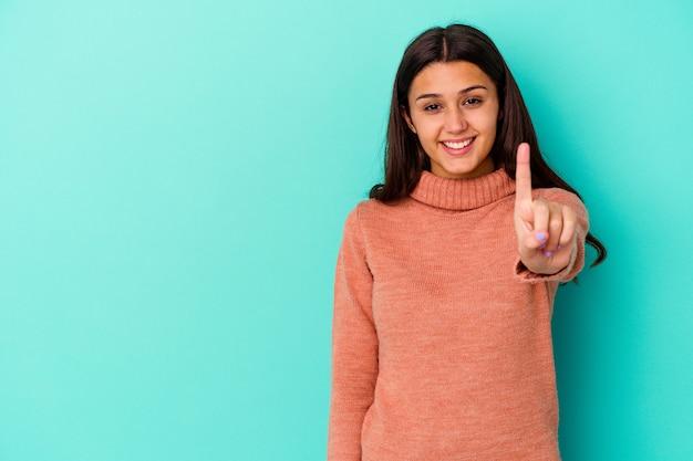 Jonge indiase vrouw geïsoleerd op blauw met nummer één met vinger.
