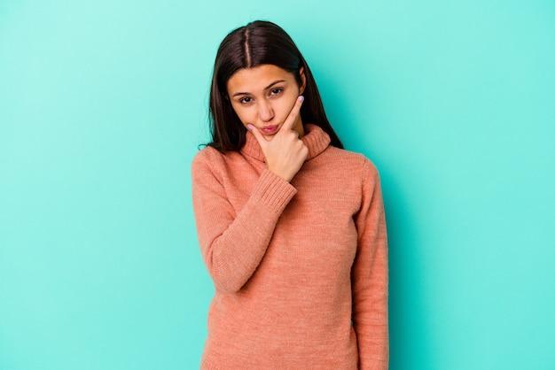 Jonge indiase vrouw geïsoleerd op blauw overweegt, het plannen van een strategie, nadenken over de manier van een bedrijf.