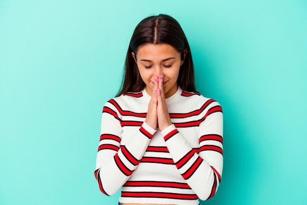 Jonge indiase vrouw geïsoleerd op blauwe achtergrond hand in hand bidden in de buurt van mond, voelt zich zelfverzekerd.