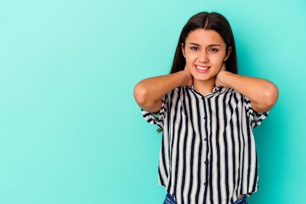 Jonge indiase vrouw geïsoleerd op blauwe muur achterkant van het hoofd aan te raken, te denken en een keuze te maken.