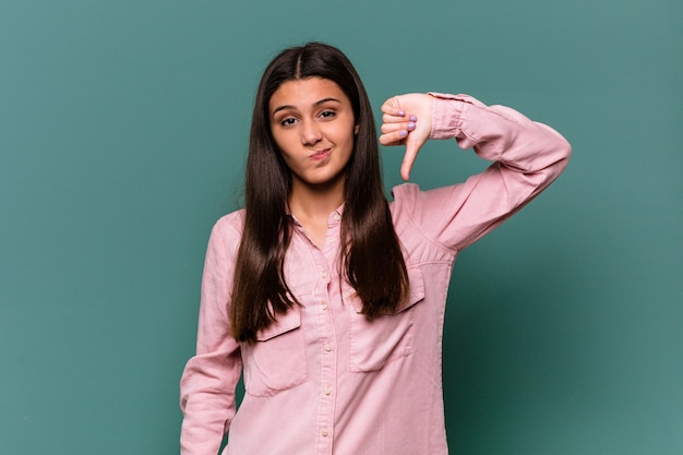Jonge indiase vrouw geïsoleerd op blauwe muur met duim omlaag, teleurstelling concept