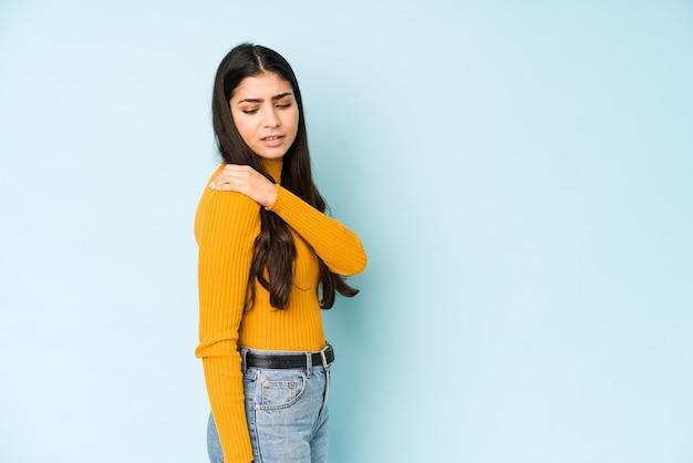 Jonge indiase vrouw geïsoleerd op blauwe muur met pijn in de schouder.