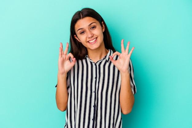 Jonge indiase vrouw geïsoleerd op blauwe muur vrolijk en zelfverzekerd tonend ok gebaar.
