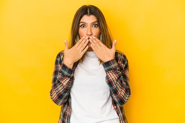 Jonge indiase vrouw geïsoleerd op gele muur geschokt bedekkende mond met handen