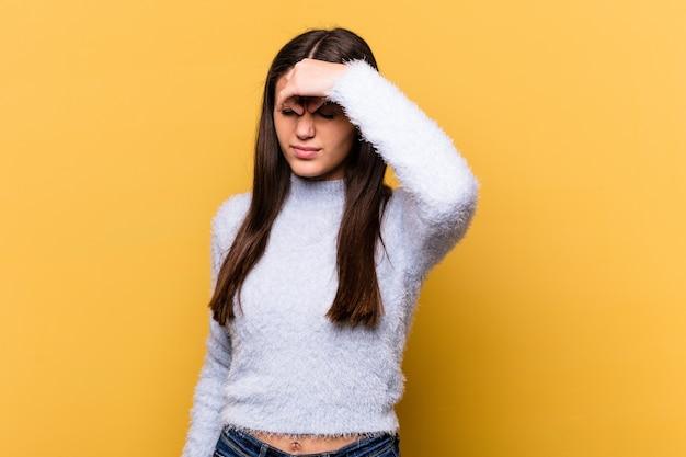 Jonge indiase vrouw geïsoleerd op gele muur met hoofdpijn, wat betreft de voorkant van het gezicht