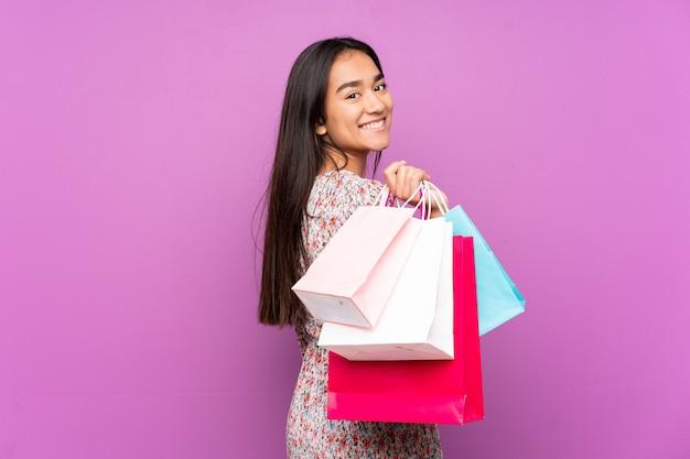Jonge indiase vrouw geïsoleerd op paars bedrijf boodschappentassen en glimlachen