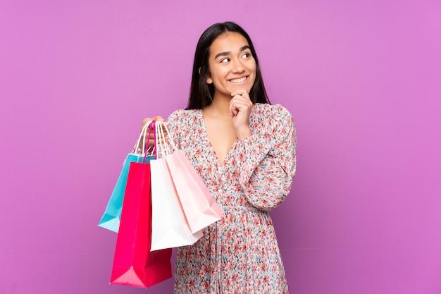 Jonge indiase vrouw geïsoleerd op paars met boodschappentassen en denken
