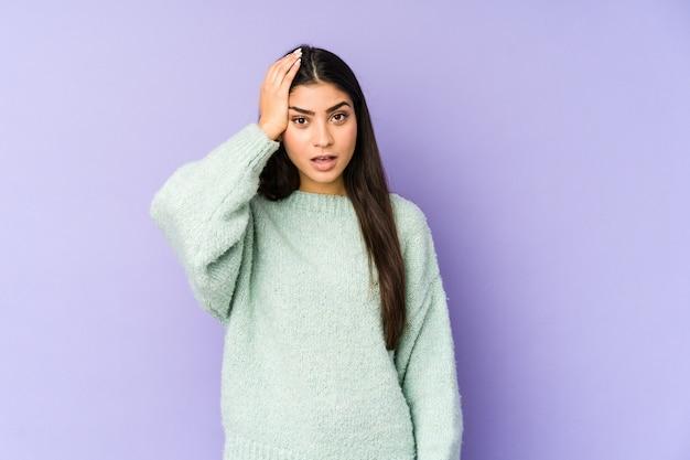 Jonge indiase vrouw geïsoleerd op paars wordt geschokt, ze heeft belangrijke bijeenkomst herinnerd.