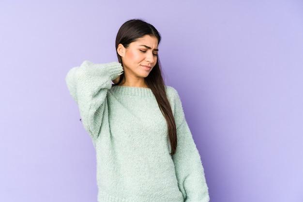 Jonge indiase vrouw geïsoleerd op paarse achtergrond nekpijn lijden als gevolg van sedentaire levensstijl.