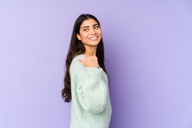 Jonge indiase vrouw geïsoleerd op paarse achtergrond punten met duim vinger weg, lachend en zorgeloos.